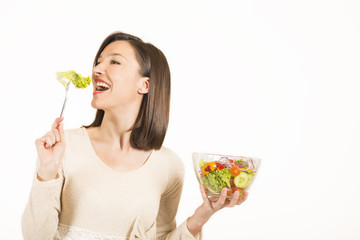 Happy young woman eating vegetables salad