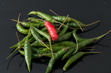 green chili peppers and red on a black background
