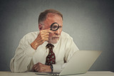 man working on computer looking through magnifying glass