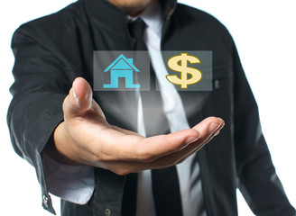 businessman holding house and money icon