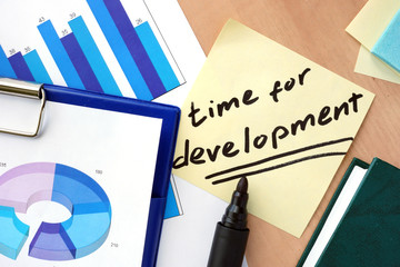 Paper with words time for development and charts.