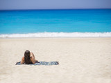 Woman relaxing on the famous Shipwreck beach in Zakynthos