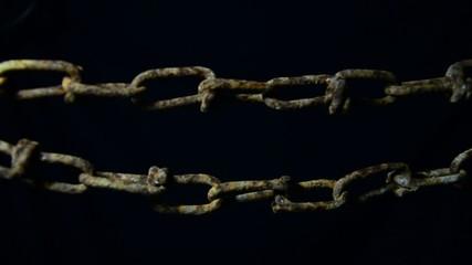 rusty chain swinging in the dark