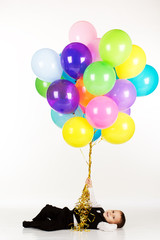 Little boy holding colorful balloons