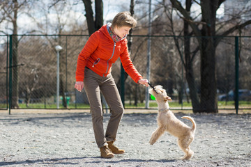 Girl in orange jacket plays with puppy
