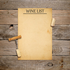Corkscrew with cork and blank wine list on old wooden background