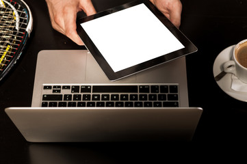 Squash rackets, black tablet, computer and coffee - Stock Image