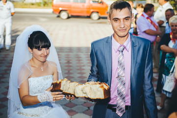 Groom holding slice of traditional wedding round loaf and bride