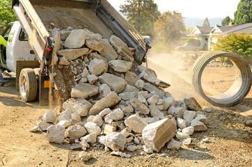 A small dump truck dumps concrete pieces