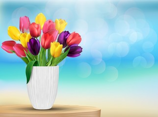 Tulip flowers in rainbow colours in a white glass on the beach