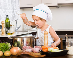 Little girl prepared soup with vegetables