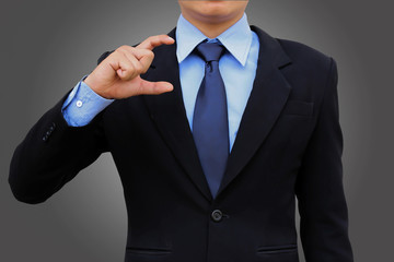 Business man holding black suit on dark background.