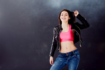 young woman hip hop dancer on the background texture dark wall