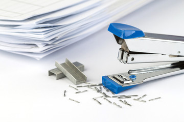 stapler and pile of papers.