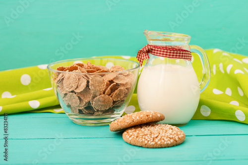 Plakat Jug of milk with muesli and cookies on blue wooden kitchen