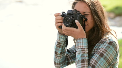 Young girl taking pictures at the park