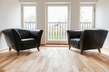 Leather black armchairs in a room