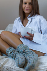 Beautiful smily woman drinking coffe on a sofa in knitted socks.