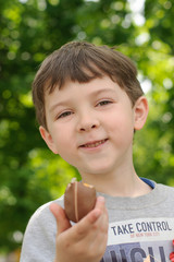 Boy eats chocolate egg and smiling