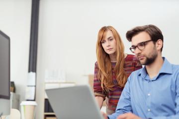 kollegen schauen gemeinsam auf laptop
