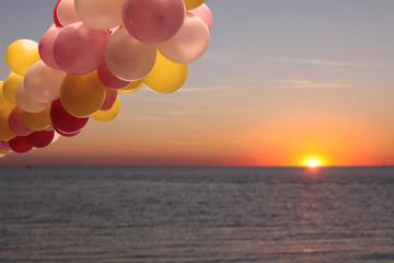 ballons am meer mit sonnenuntergang