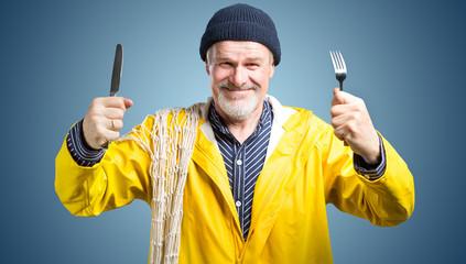 hungriger Seemann mit Messer und Gabel bereit zum Essen