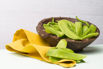 Snow peas on wooden bowl