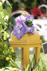 Yellow lantern decorated with purple orchids in a garden