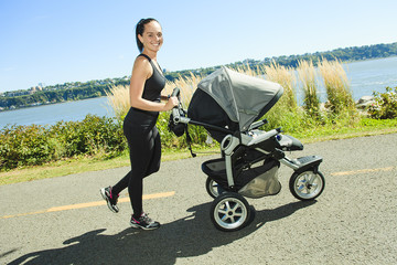 A Young mother jogging with a baby on the buggy
