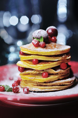 Stack of pancakes with berries and sugar powder