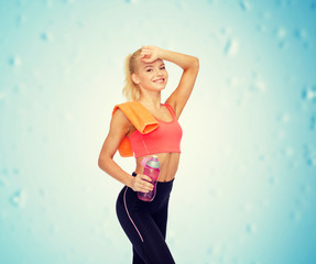 smiling sporty woman with towel and water bottle