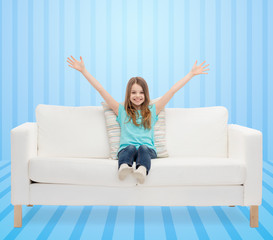 happy girl sitting on sofa with raised hands