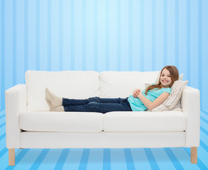 smiling little girl lying on sofa