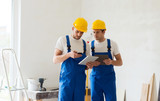 builders with tablet pc and equipment indoors