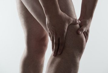 Young male massaging his sore knee. Joint disease.