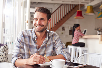Young man having breakfast in a cafe