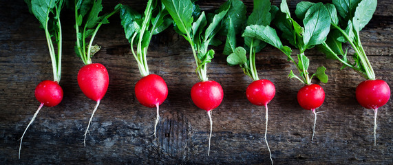 Bunch of fresh radishes on old wooden table - organic food