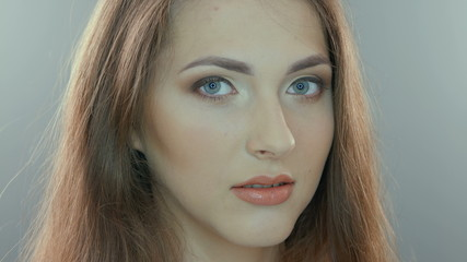 Video portrait of a young woman, isolated on gray