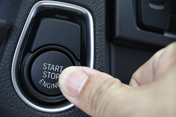 Finger pressed the button to start the car