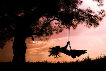 silhouette of happy young woman on a swing with sunset