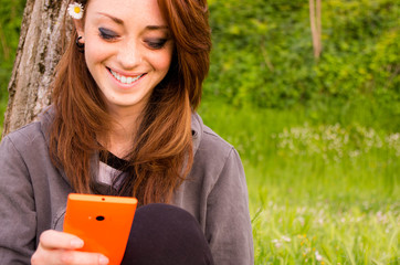 girl laughs looking at her phone in a park - lifestyle concept