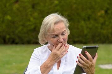 Attraktive Rentnerin genießt ihre Freizeit mit einem Tablet