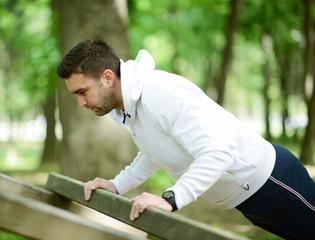 Male athlete exercising push up outside