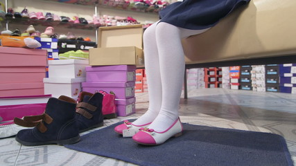 Little girl trying on new flats in childrens shoe store