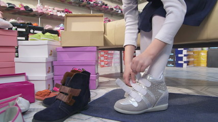 Child trying on new sneakers for girls in shoe store