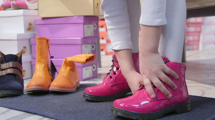 Child trying on new pink boots for girls in children shoe store