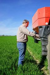 Getreidedüngung - Landwirt justiert Wurfteller vom Düngerstreuer