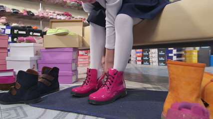 Little girl trying on new pink boots in children shoe store