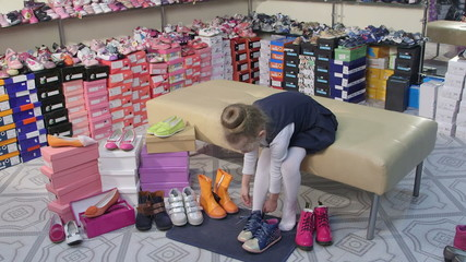 trying on new shoes for junior girls in children shoe store