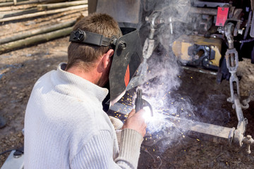 welder working with electrode at semi-automatic arc welding